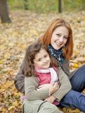 Two sisters sitting on the leafs in the park. Royalty Free Stock Image