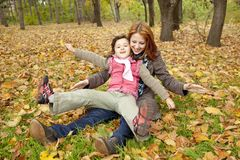 Two sisters sitting on the leafs in the park. Royalty Free Stock Photos