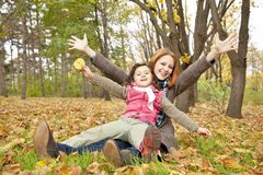 Two sisters sitting on the leafs in the park. Stock Photo