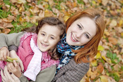 Two sisters sitting on the leafs in the park. Royalty Free Stock Photo