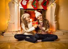 Two sisters sitting next to fireplace with Christmas gifts Stock Photo