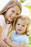 Two sisters sitting outdoors smiling Stock Photo