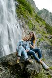 Two sisters sitting on the stone on waterfall background stock image