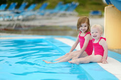 Two sisters sitting by a swimming pool Royalty Free Stock Photography