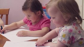 Two sisters sitting at a table. With sheets of paper. Woman brings them color pencils . Then they start to draw stock video