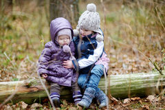 Two sisters sitting on a tree Stock Photo