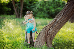 Two sisters sitting on a tree stump in a beautiful park in the summer Stock Image