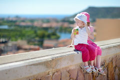 Two sisters sitting on a wall enjoying a view Stock Image