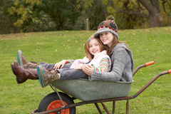 Two Sisters Sitting In Wheelbarrow Stock Photography