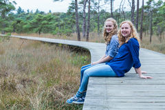 Two sisters sitting on wooden path in forest Royalty Free Stock Photo