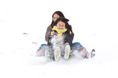 Two sisters sledging holding each other Stock Image
