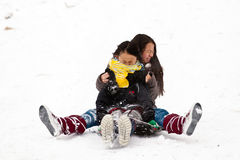 Two sisters sledging holding each other Royalty Free Stock Image