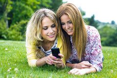 Two sisters with smartphone at the park Stock Image