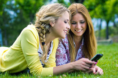 Two sisters with smartphone at the park Stock Images
