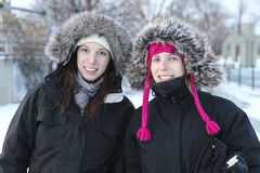 Two sisters smiling. Picture of two sisters wearing winter coats and wool hats during a cold winter day Royalty Free Stock Photos