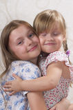 Two sisters. Smiling and huging each other Stock Photos