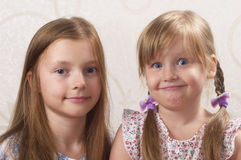 Two sisters. Smiling and looking funny way over blurred background Royalty Free Stock Photo