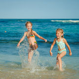 Two sisters splashing on the beach Royalty Free Stock Photography