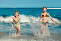 Two sisters splashing on the beach Stock Images