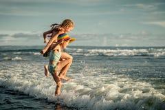 Two sisters splashing on the beach Stock Photos