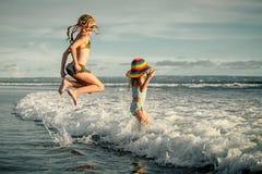 Two sisters splashing on the beach Royalty Free Stock Photos