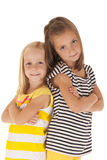 Two sisters standing back to back with arms folded Royalty Free Stock Images