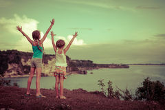 Two sisters standing on the beach and pulled up his hands Stock Photo