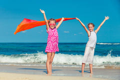 Two sisters standing on the beach and pulled up his hands Royalty Free Stock Photography