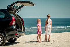 Two sisters standing near a car on the beach stock photography