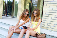Two sisters steps of the Institute watching a movie on tablet in social networks, with glasses and denim shorts Stock Photography