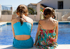 Two sisters stitting by the pool Stock Images