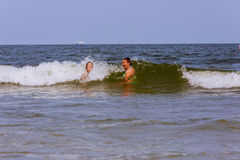Two sisters swim in the ocean on waves Stock Photo
