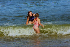 Two sisters swim in the ocean on waves Royalty Free Stock Photography