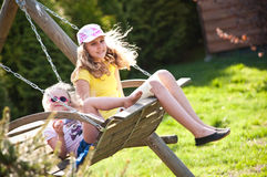 Two sisters on swing. Older and younger sister on wooden seat swing in garden Stock Photo