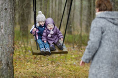 Two sisters swinging outdoors Royalty Free Stock Photography