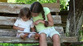Two sisters with tablet PC sits on the swing bench. Two little girls with tablet computer sits on the swing bench stock footage