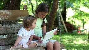 Two sisters with tablet PC sits on the swing bench. Two little girls with tablet computer sits on the swing bench in garden stock video footage