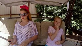 Two sisters talk on the swings in the summer. HD stock footage