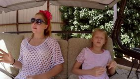 Two sisters talk on the swings in the summer. HD stock video footage