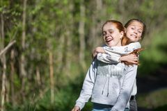 Two sisters  teen girls friends hugs and having fun in the Park. Stock Photography