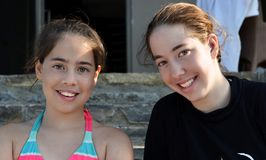 Two sisters. Two teenage sister (aged 16 and 12) relaxing after a swim in the pool Stock Photography