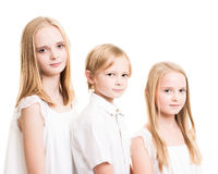 Two Sisters And Their Brother Dressed in White in the Studio Stock Photo