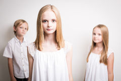 Two Sisters And Their Brother Dressed in White in the Studio Royalty Free Stock Images