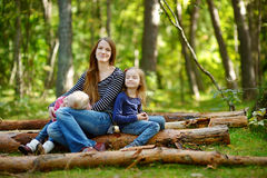 Two sisters and their mother sitting on a big log Royalty Free Stock Image