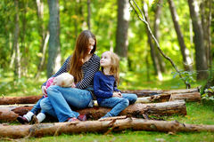 Two sisters and their mother sitting on a log Royalty Free Stock Images