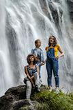 Two sisters with their mother sitting on the stone on waterfall royalty free stock image
