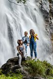 Two sisters with their mother sitting on the stone on waterfall royalty free stock images