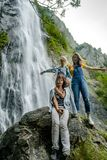 Two sisters with their mother sitting on the stone on waterfall stock photos