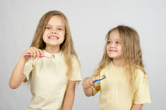 Two sisters with toothbrushes Stock Images