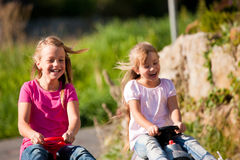Two sisters with toy cars Stock Photo